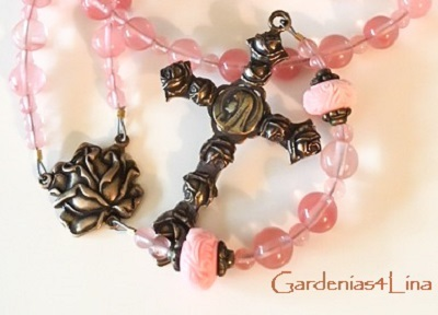Cherry quartz, hand carved shell and handcrafted bronze fixtures make this rosary based on the poem, Christ Has No Body, written by Teresa of Avila.